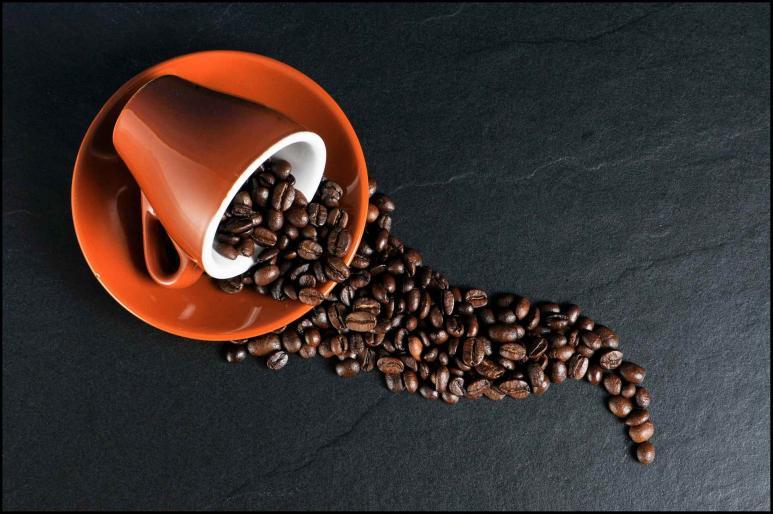 Kaffeebohnen kullern aus einer Tasse